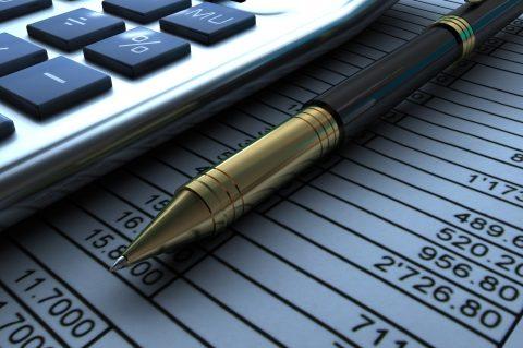 Closeup view of a calculator, pen and financial report