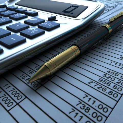 Closeup view of a calculator, pen and financial report