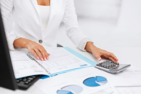 Women doing calculations with calculator looking at financial documents