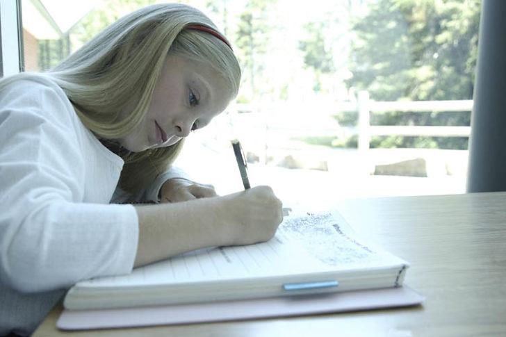 Girl writing in a book