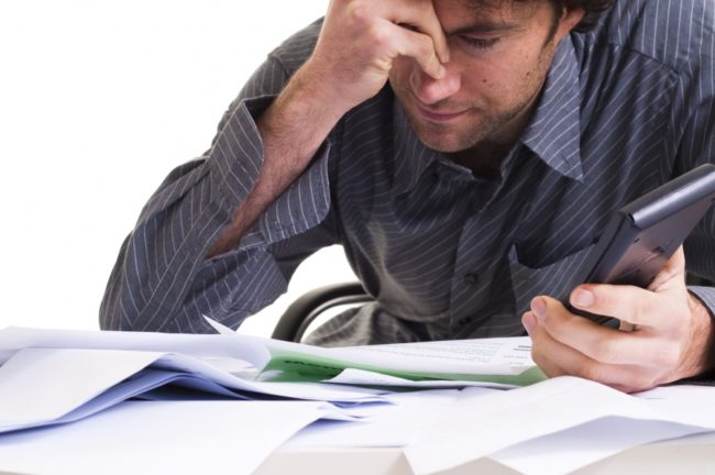 common accounting mistakes - business owner doing his own accounting looking frustrated