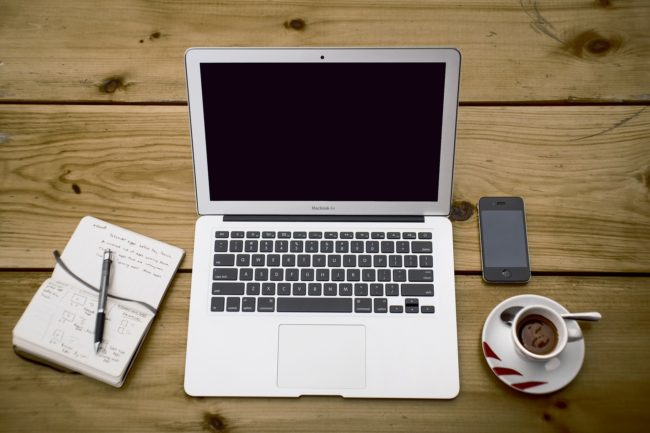 Photo of a Laptop on wooden table with coffee, phone and notes