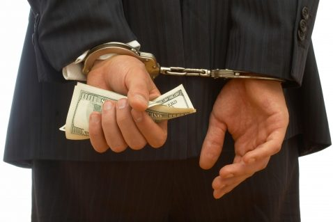 Man with handcuffs behind his back with money is his hands
