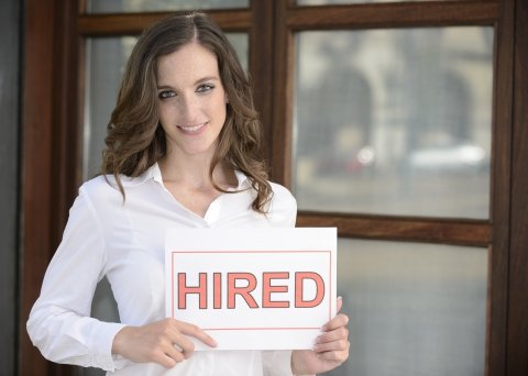 Women holding a sign saying hired
