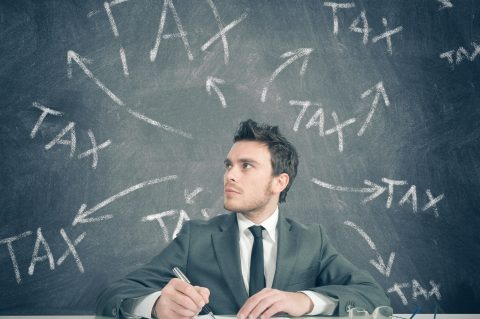 "Man at desk with the word ""Tax"" dawn on chalkboard behind him"