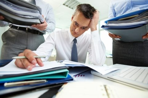 Man swamped in financial paperwork with two people dropping off more work
