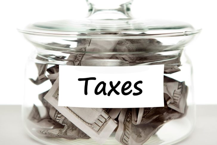 Money in a glass jar for paying Taxes