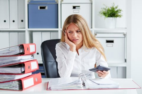 Business owner sitting at her desk looking frustrated with calculator in hand