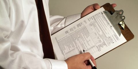 Man with tax forms on a clipboard