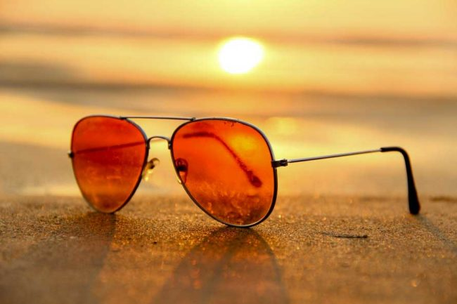 Sunglasses in the sand during a sunset