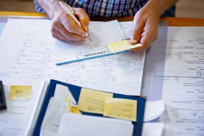 understanding business financial statements - Man filling out financial statements