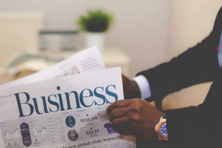 Black man in a dress suit holding the business section of the news paper