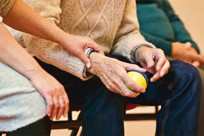 Holding an elderly person's arm as they are both seated.
