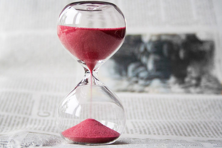 Red sand running through an hourglass