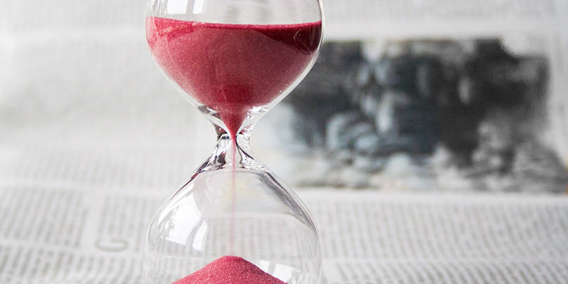 Red sand running through an hourglass
