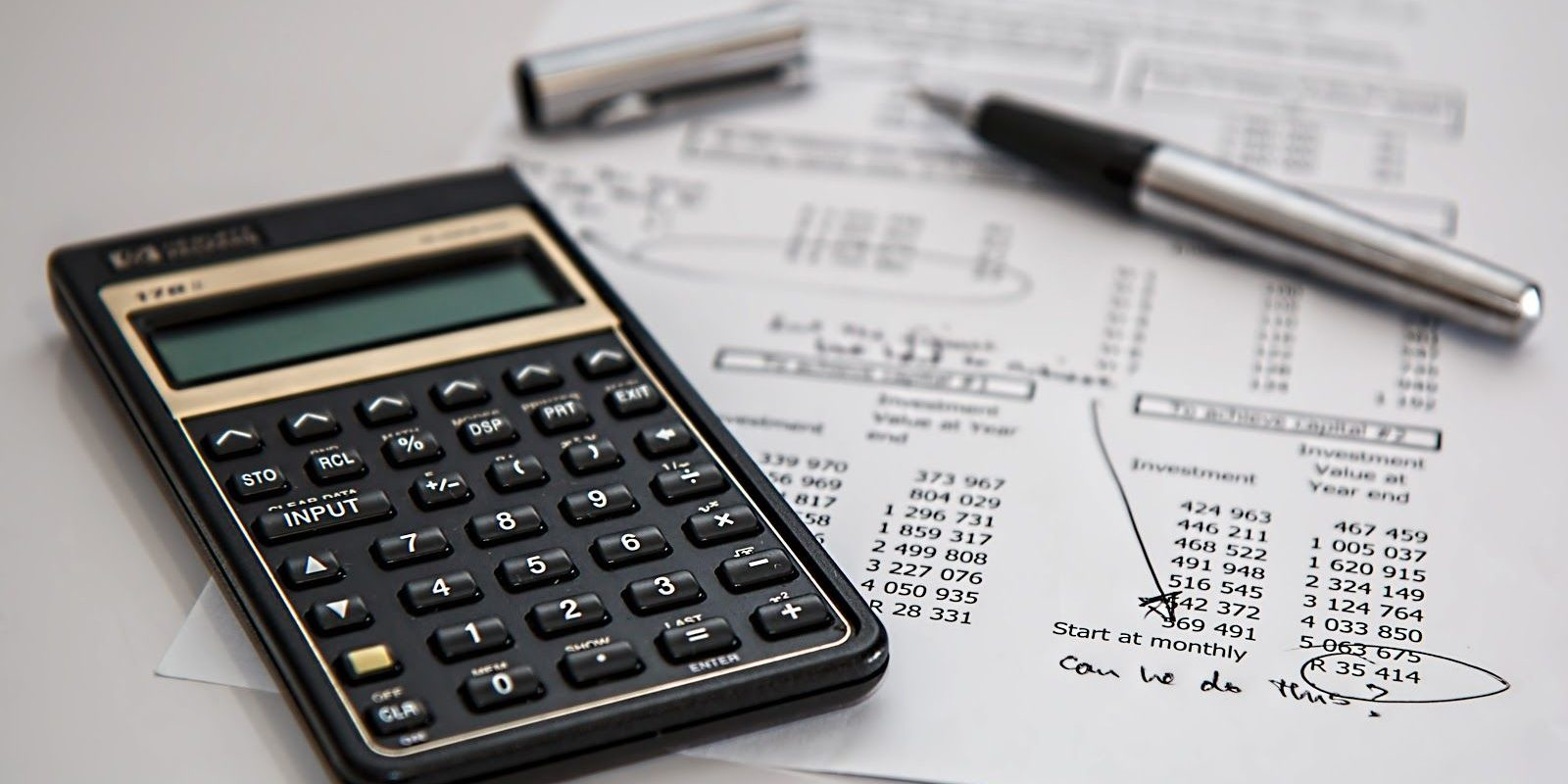 Image of a calculator and a pen sitting on top of an accountants desk with Quickbooks notes