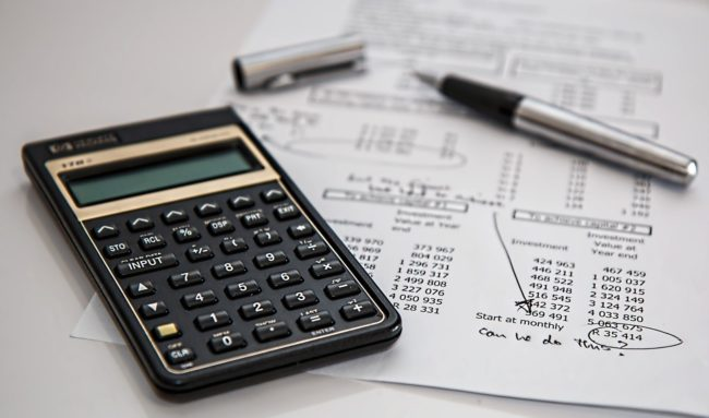 accounting for small business owners - mage of a calculator and a pen sitting on top of an accountants desk with Quickbooks notes